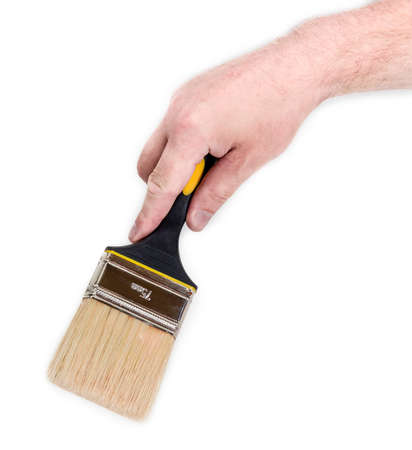 Wide flat paintbrush with rubberised black and yellow handle in mans hand on a light background. Isolation.