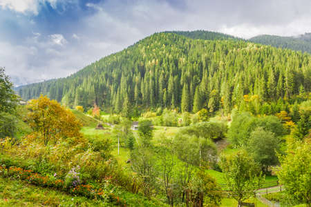 Mountain landscape with with rural outbuildings, forests and mountain ranges against the sky with clouds autumn. Stock Photo