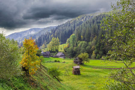 Mountain landscape with with rural outbuildings, forests and mountain ranges against the sky with storm clouds. Stock Photo