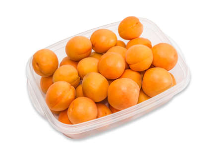 Transparent plastic tray with ripe apricot closeup on a light background. Isolation. Standard-Bild