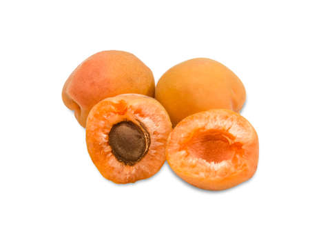 Three large ripe apricot, one of which is cut in half closeup on a light background. Isolation. Stock Photo