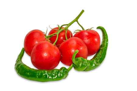 fascicule: Branch of tomatoes with dew drops and two green peppers chili on a light background. Isolation. Stock Photo