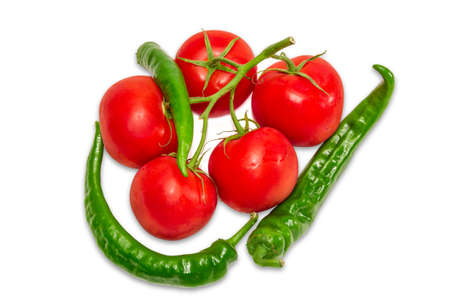Branch of tomatoes with dew drops and several green peppers chili on a light background. Isolation.