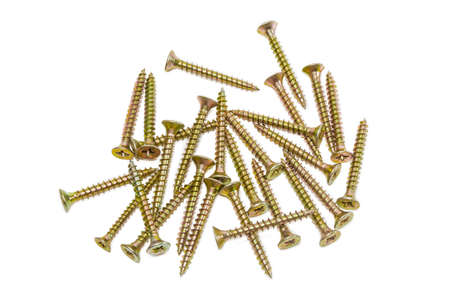 Several wood screws with countersunk head, covered with a yellow protective anticorrosion coating of zinc galvanization, on light background. Isolation. Stock Photo