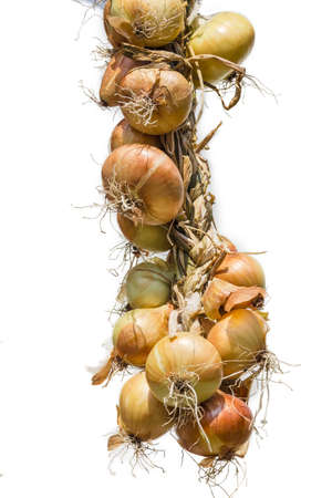 Bundle of onions, wattled in the form of a wreath on a light background. Isolation. Stock Photo