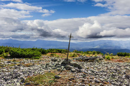 mountain ranges: Mountain autumn landscape with direction indicator tourist trail, scatterings of stones, thickets of mountain pine in the foreground, mountain ranges and sky with clouds
