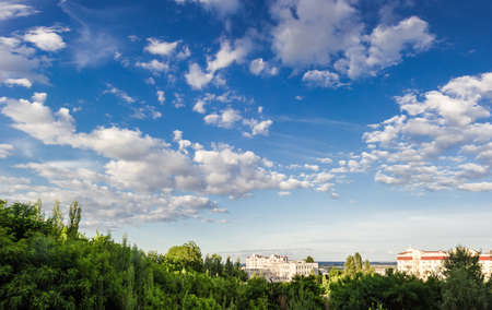 wetness: Sky with clouds with trees in the foreground and the buildings in the background summer in afternoon