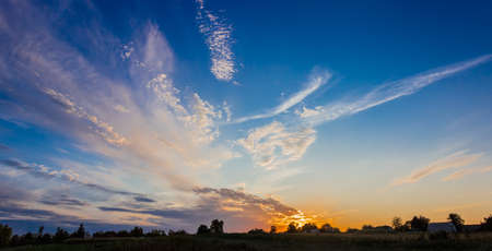 floccus: Sunset in the countryside with cirrus fibratus clouds and cirrus floccus clouds