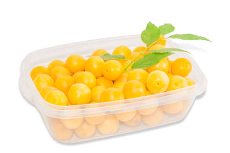 myrobalan: Transparent plastic tray with ripe yellow cherry plum and a branch with leaves on a light background. Isolation. Stock Photo