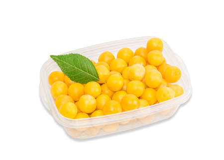myrobalan: Transparent plastic tray with ripe yellow cherry plum on a light background. Isolation.