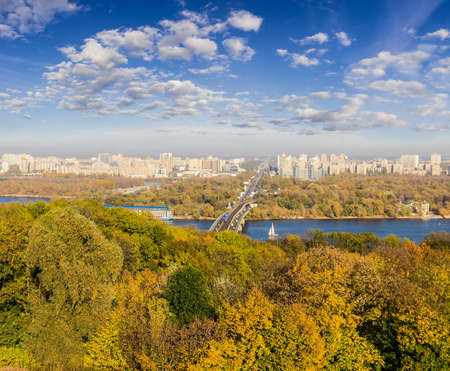 multi storey: Autumn cityscape with yellowed leaves on the trees, the river and the bridge across it in the foreground, urban multi storey buildings and sky with clouds in the background. Kiev, Ukraine.