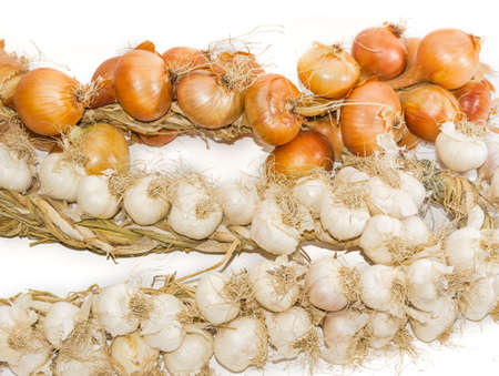 Bundle of onions and garlic, wattled in the form of a wreaths closeup on a light background. Isolation.