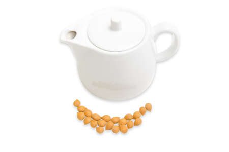 apricot kernels: Shelled apricot kernels and white ceramic teapot on a light background. Isolation. Stock Photo