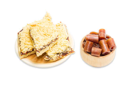 pastila: Pieces of apricot pie on a plate and apricot pastila in wooden sweets dish on a light background. Isolation