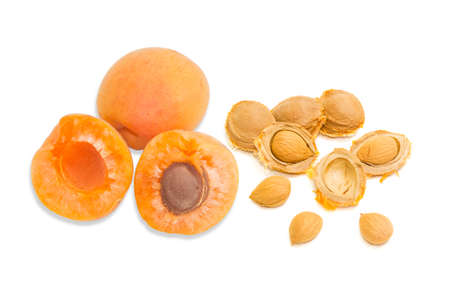 yellow: Two ripe apricot, one of which is cut in half and several apricot kernels closeup on a light background. Isolation.