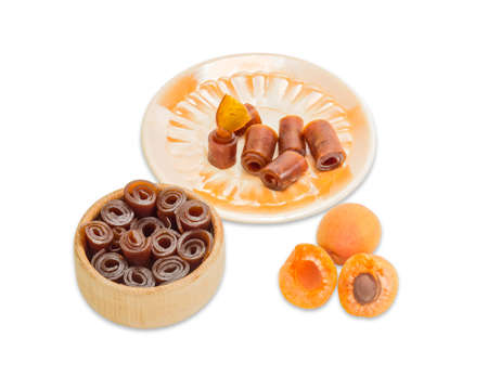 convolute: Apricot pastila convolute into rolls in wooden sweets dish, several pieces of pastila and on a yellow saucer and two ripe apricot on a light background. Isolation