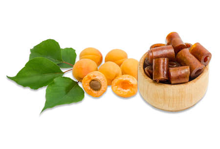pastila: Apricot pastila in wooden sweets dish and several ripe apricot with a branch on a light background. Isolation