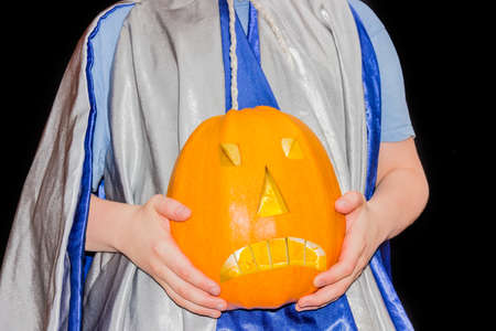 halloween costume: Symbol of Halloween - jack-o-lanterns, made of yellow hollowed-out pumpkin, in the hands of the boy in Halloween costume