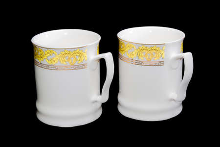 aureate: Two white porcellaneous cups with yellow and aureate floral ornaments on a black background. Isolation. Stock Photo