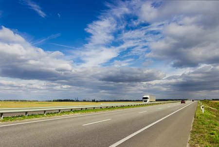 cirrus clouds: Highway among fields on a background of sky with cumulus and cirrus clouds Stock Photo