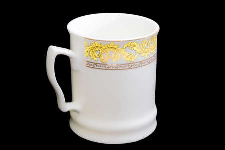 aureate: White porcellaneous cup with yellow and aureate floral ornaments on a black background. Isolation.