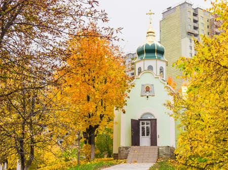 multi storey: Small orthodox church among trees with yellow leaves on a background of multi storey building under construction in cloudy day Stock Photo