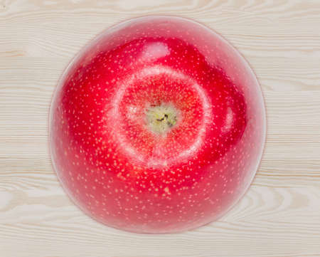 sappy: Round ripe red apple on a wooden surface closeup