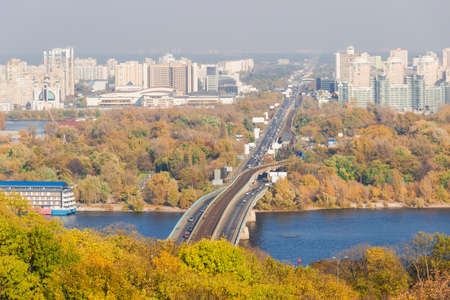multi storey: Autumn cityscape with yellowed leaves on the trees, the river and the bridge across it in the foreground, urban multi storey buildings and sky in the background. Kiev, Ukraine. Stock Photo