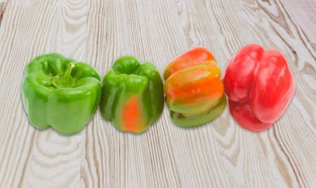 bell peppers: Several green, yellow and red fresh bell peppers on a wooden surface