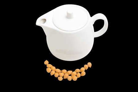 apricot kernels: Shelled apricot kernels and white ceramic teapot on a black background. Isolation. Stock Photo