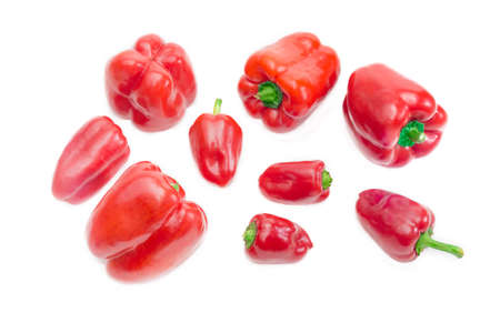 bell peppers: Several fresh red bell peppers different sizes on a light background. Isolation. Stock Photo