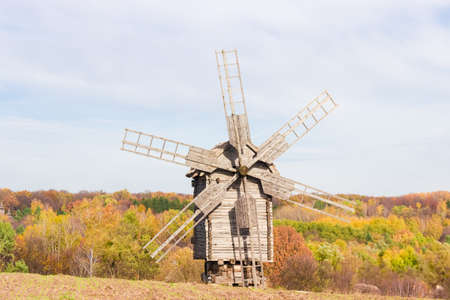 ethnographical: Old windmill on a background of forest and sky in autumn day. National Museum of Ukrainian Architecture and Culture, Kiev, Ukraine..