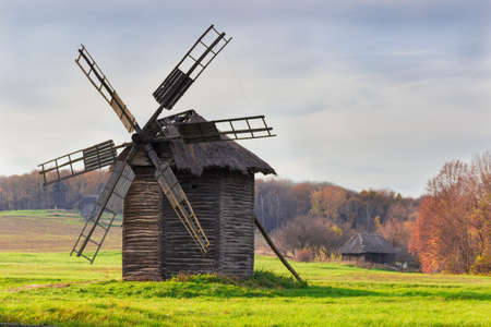 ethnographical: Old windmill on a background of forest and sky in autumn evening. National Museum of Ukrainian Architecture and Culture, Kiev, Ukraine..