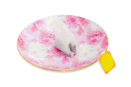 tea filter: One tea bag made of filter paper with black tea and yellow paper label on a pink saucer on a light background closeup. Isolation.