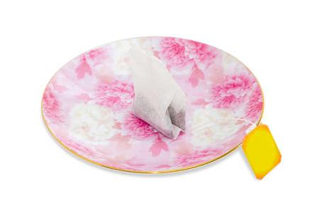 papel filtro: Una bolsa de t� hecho de papel de filtro con t� negro y la etiqueta de papel amarillo en un plato de color rosa sobre un fondo claro de cerca. Aislamiento.