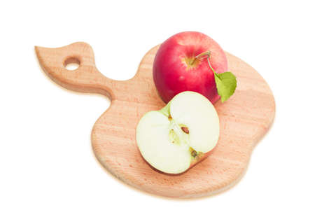 half apple: One whole red ripe apple with leaf and half apple on a cutting board which made of beech wood and has the form of apple. Isolation on a light background Stock Photo