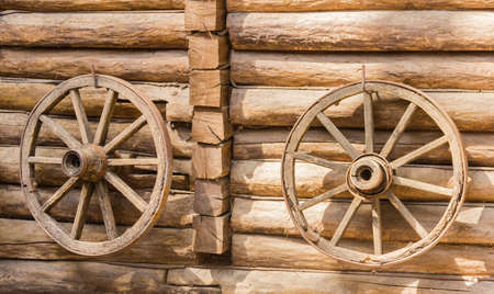 spoked: Two old wooden spoked cartwheels with metal tires hanging on the wall of the wooden house