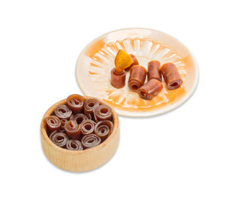 pastila: Apricot pastila convolute into rolls in wooden sweets dish and several pieces on a yellow saucer on a light background.