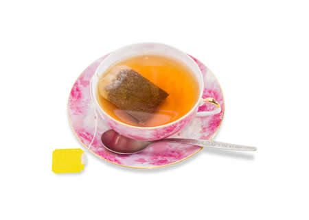 teaspoon: Pink cup with tea and tea bag with a yellow label and a teaspoon on a saucer with a pink floral patterns on a light background