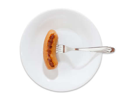 veal sausage: Grilled banger in natural casing impaled on a fork on a white dish on a light background. Stock Photo