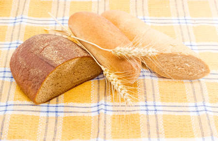 long loaf: Half a oblong loaf of brown bread from rye and wheat flour, half a long loaf of wheat bread with bran, loaf of multigrain bread and two wheat spikes on a checkered tablecloth Stock Photo