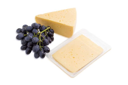 dark blue: Piece of cheese, sliced cheese in transparent plastic tray and bunch of dark blue table grapes on a light background.