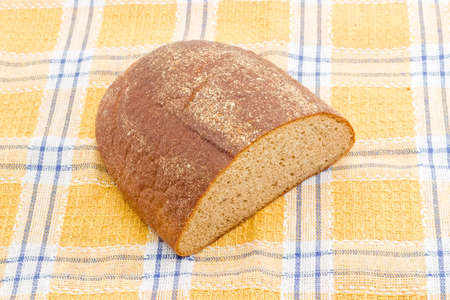 oblong: Half a oblong loaf of brown bread from rye and wheat flour closeup on a checkered tablecloth. Foto de archivo