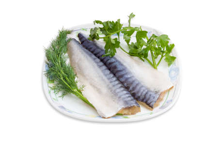 Two fillet of salted atlantic mackerel with removed a thin skin, branches of a dill and parsley on a white dish with ornament on a light background.
