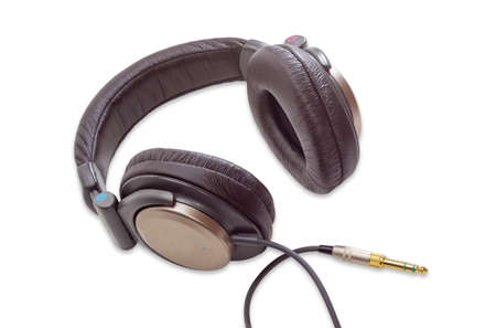 noise isolation: Light brown full size circumaural headphones with soft headband and yellow phone audio connector on a light background. Isolation.