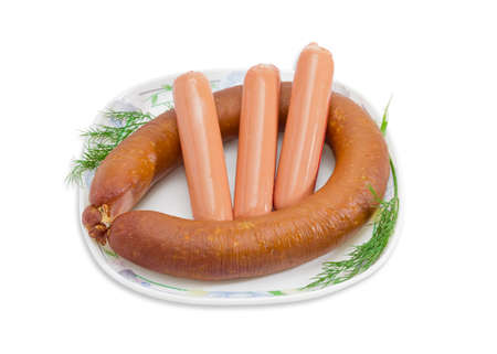 broiling: One ring smoked sausage in natural casing, three uncooked bangers in artificial casing and two branches of dill on a white dish with ornament on a light background