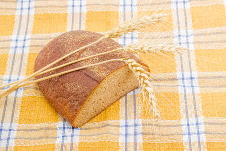 whole wheat: Half a oblong loaf of brown bread and three wheat spikes closeup on a checkered tablecloth. Stock Photo