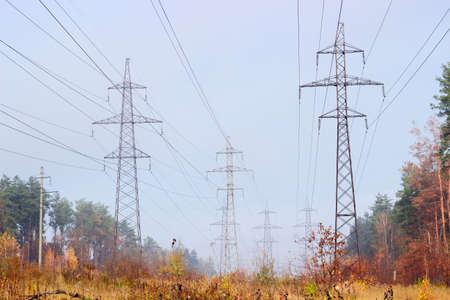 conductors: Transmission towers and wire conductors of several high voltage overhead power lines among autumnal forest Stock Photo