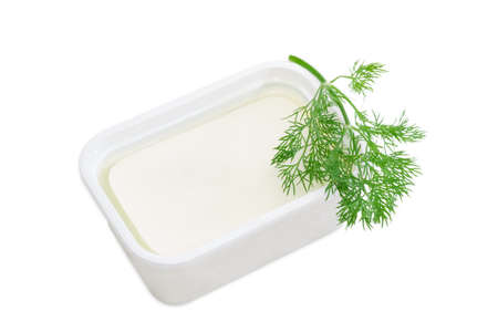 brine: Rectangular container of feta cheese in a brine and a branch of a dill on a light background