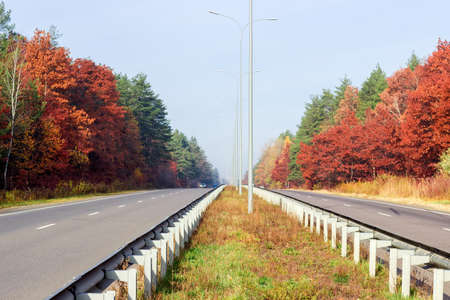 guardrails: View from of the road of the motorway with asphalt road surface and road surface marking, lampposts, traffic barriers and forest on both sides from a median strip autumn morning Stock Photo